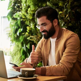 Man on laptop with coffee signing agreement