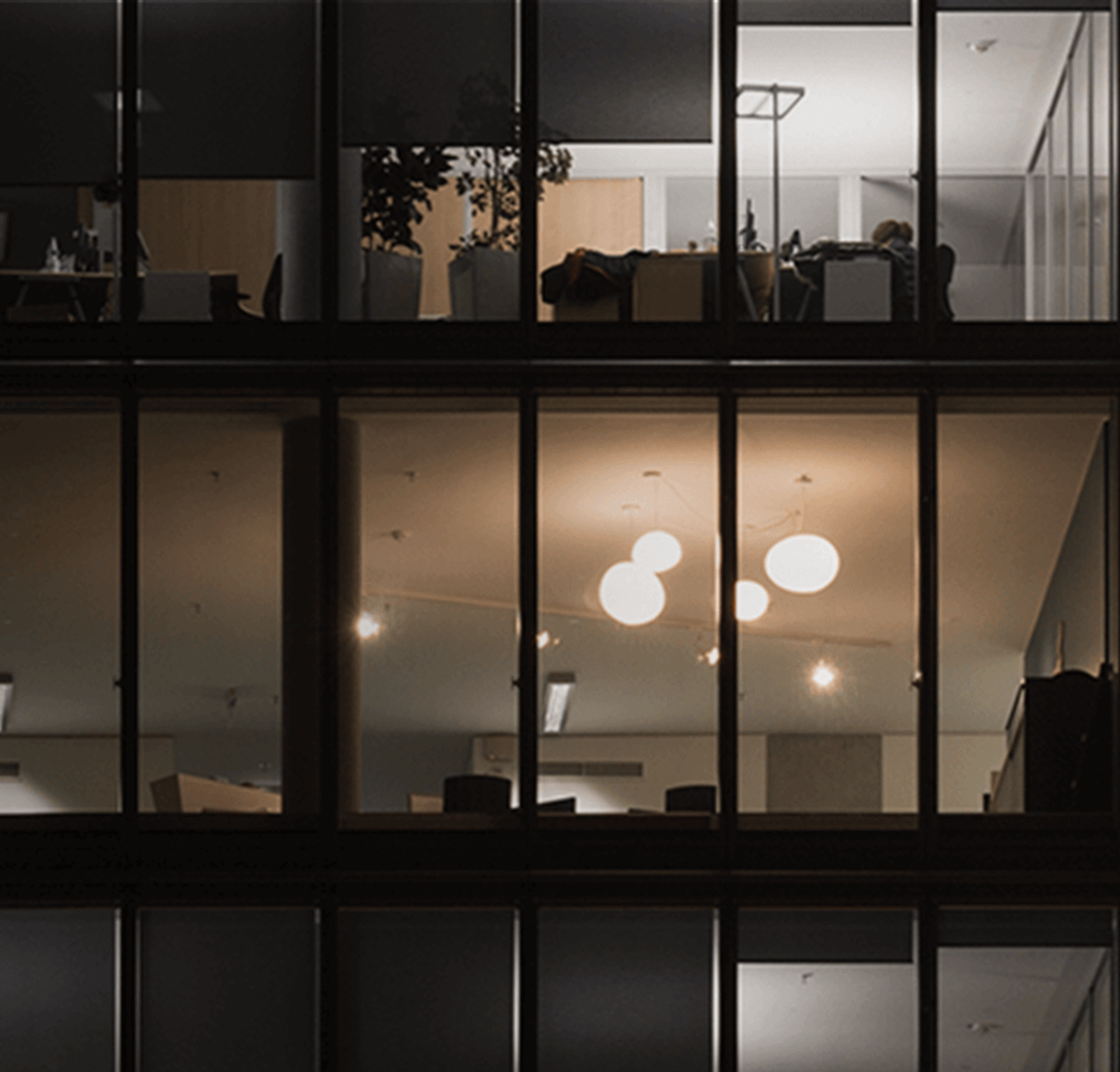 An image of three mostly dark floors in a multi-story office building at night.