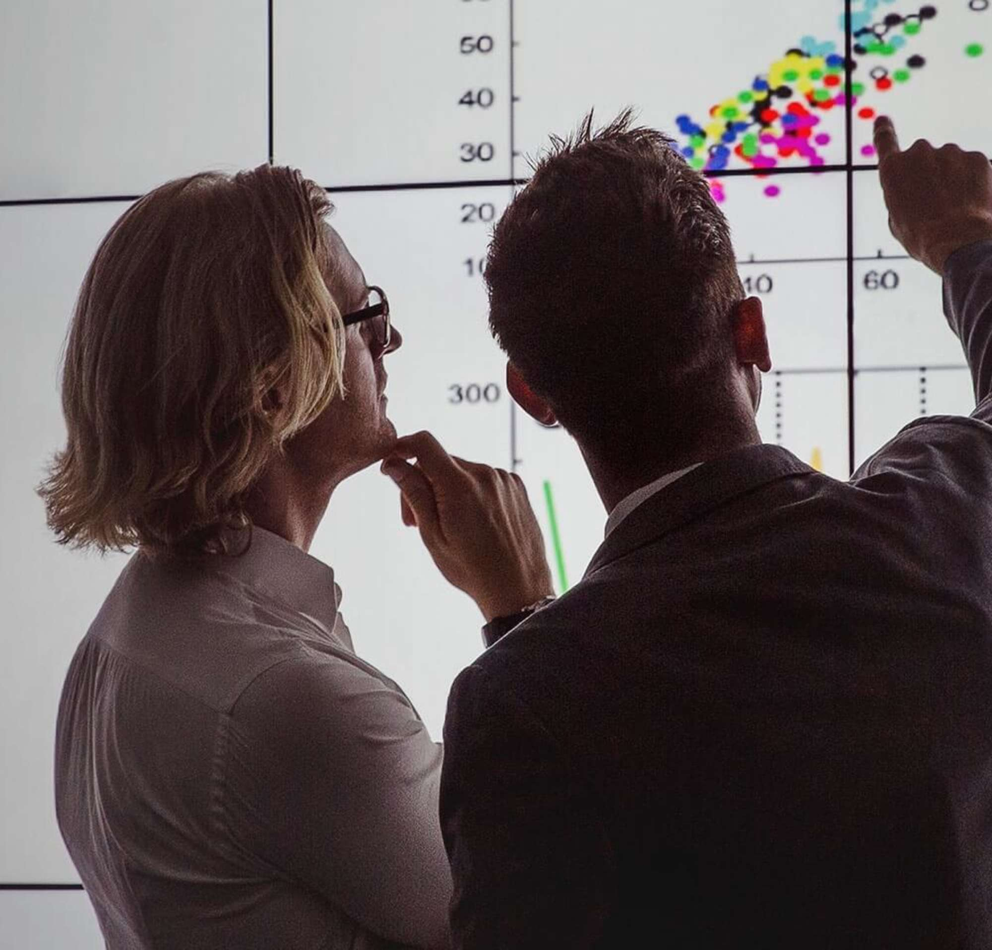 Two people analysing a contract on a large screen with the power of AI.
