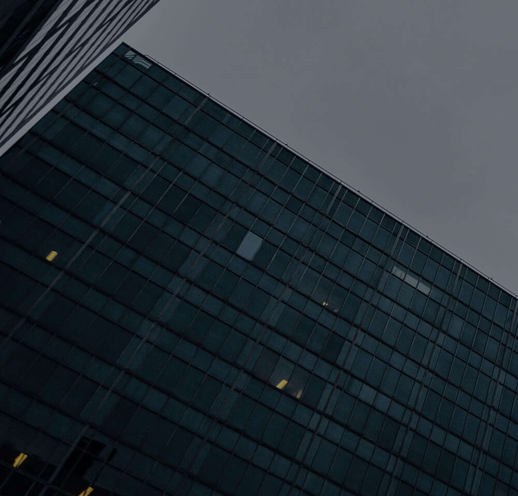 A photo from the ground of a skyscraper and another office building in the evening light on a cloudy day.