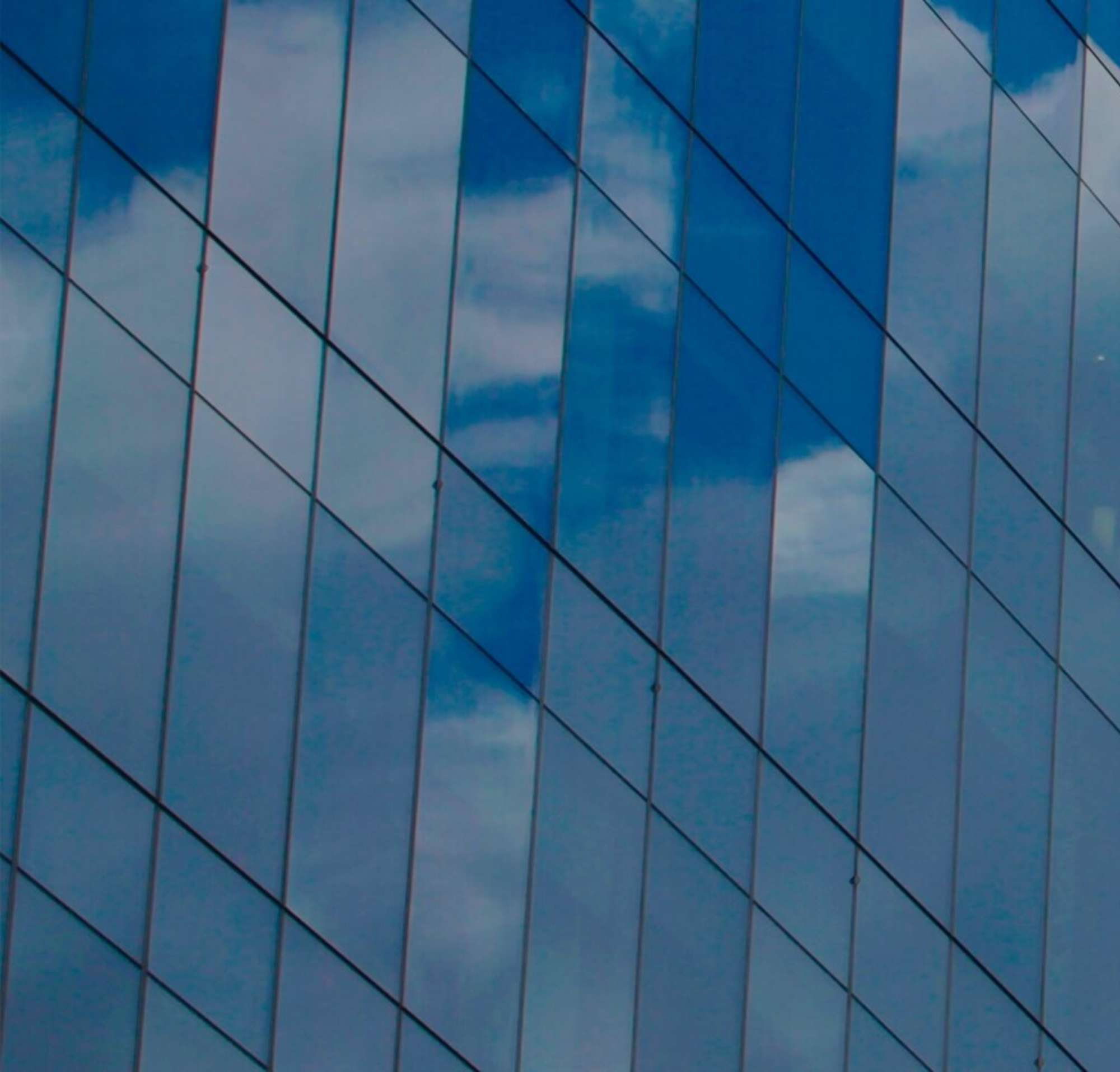 Glass windows on a high rise building, reflecting clouds.