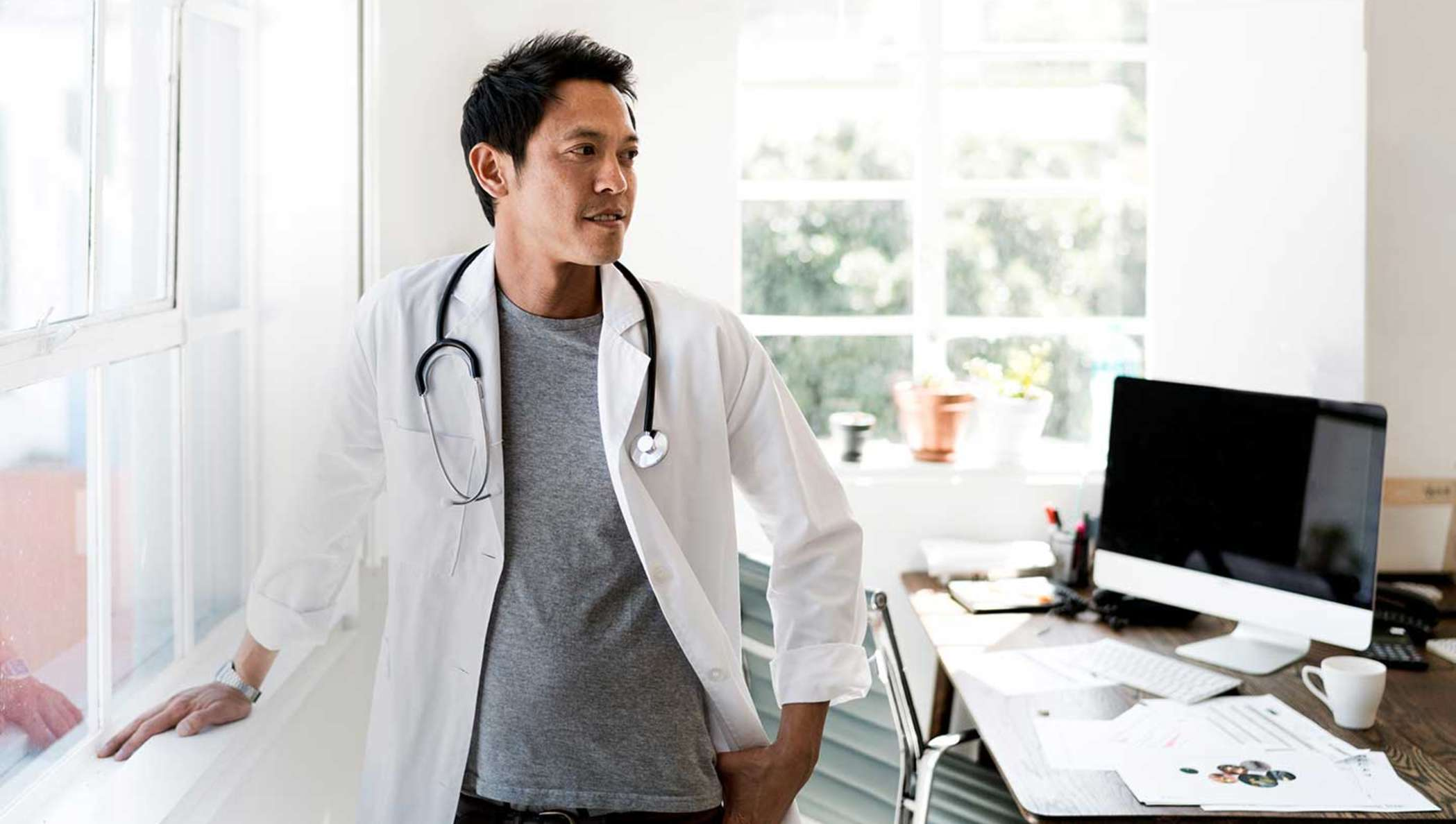 Doctor next to an office window, looking past his desk.