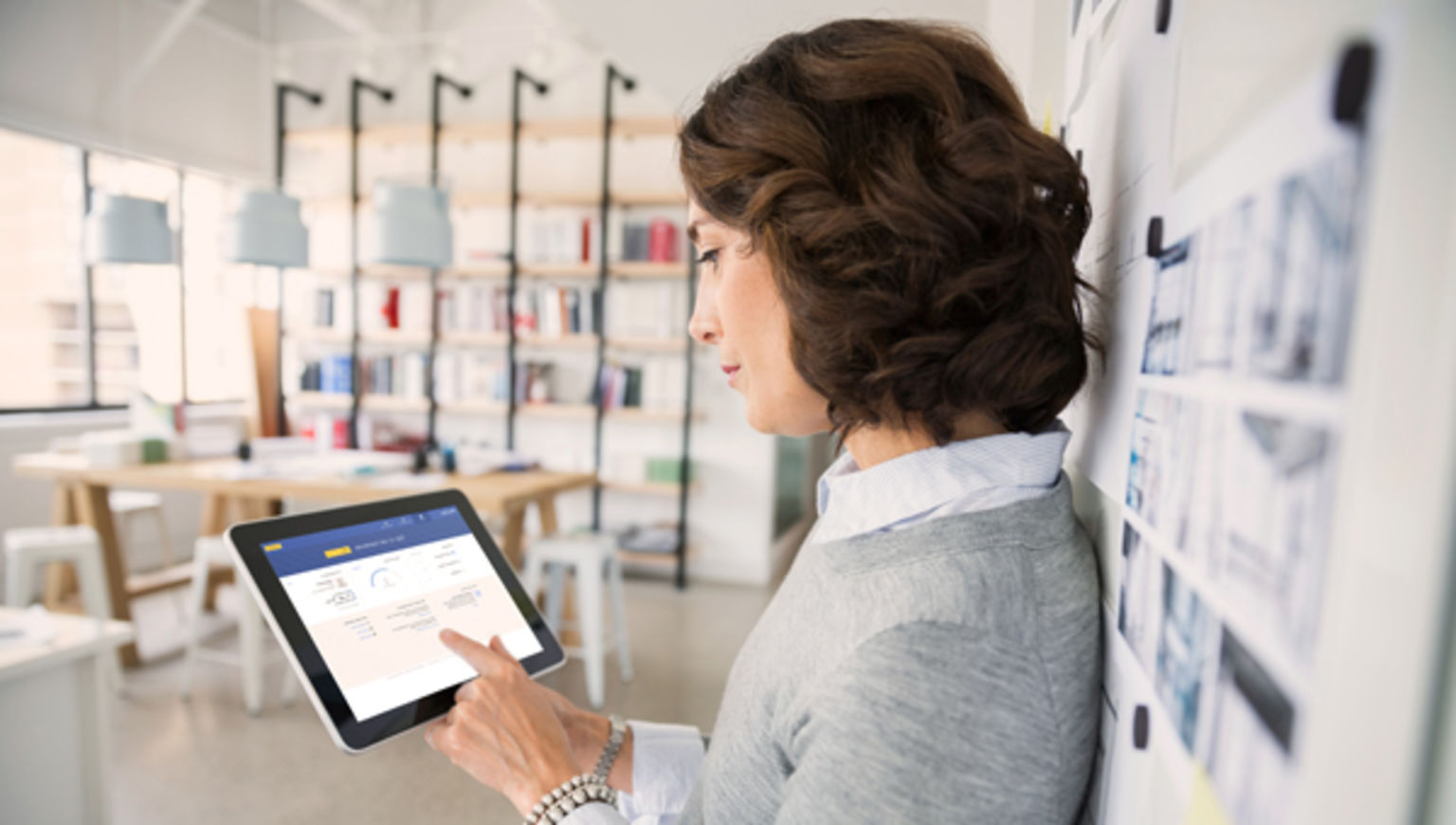 A woman leans against a wall in a naturally lit room to access DocuSign online in Australia.